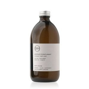 A brown bottle of bath soak from Bath House, with a Patchouli and Black Pepper fragrance.