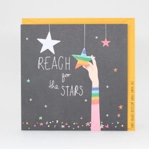 A card with a dark background and multi coloured shiny stars, spots and hearts sprinkled around. An arm reaches for a rainbow star and the words Reach for the stars