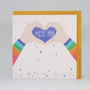 A card with two hands forming a heart with the words miss you in the heart