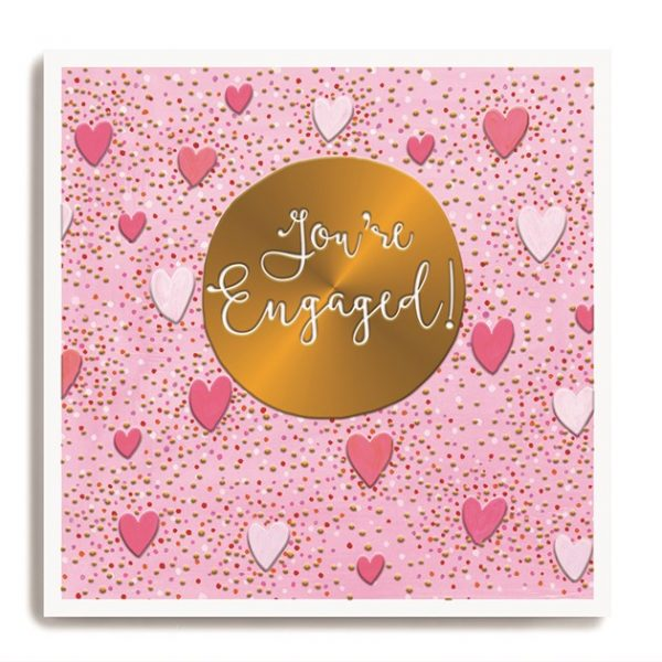 A square card with a pink background which is covered in dots and hearts. In the centre of the card is a gold disc which has been embossed with the words You're Engaged on it.