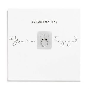 A white square card with a little rectangle which has an image of an engagement ring on it which has been finished with diamante. The words Congratulations You're Engaged areprinted on the card.
