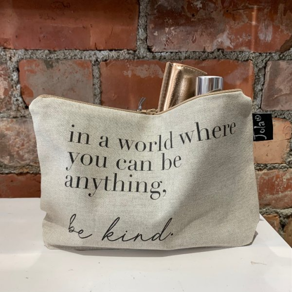 A beige coloured cotton make up bag with metal zip and the words In a world where you can be anything, Be Kind printed on it.