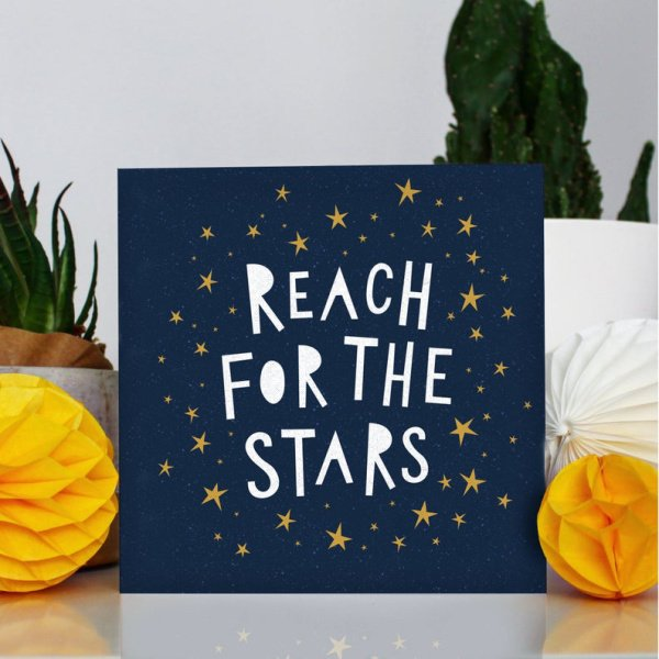 A lovely square card with the words 'Reach for the Stars' printed in white on a dark blue background with golden stars printed around it.