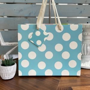 A large blue and white polka dot gift bag with a white cotton ribbon handle and matching gift card.