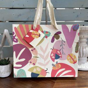 A colourful landscape gift bag with a bug design pattern. From british designer Caroline Gardiner