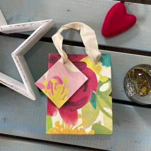 A lovely small gift bag with a painted flower design, with a cotton ribbon handle and matching gift tag.