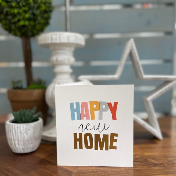 A white card with the words Happy New Home printed in contrasting colours, embossed and with gold foil effect.