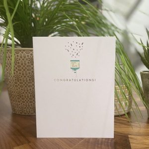 A white card with an embossed colourful party popper with woo hoo printed on it and the word congratulations printed in gold