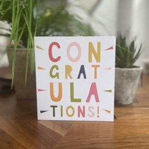 A white card with congratulations in multi coloured letters