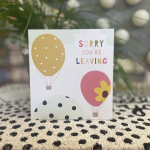 A leaving card with brightly coloured balloons and sorry you're leaving in multicoloured lettering