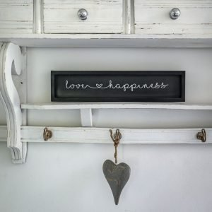 A black wooden sign with a black frame and white caligraphy reading love and happiness