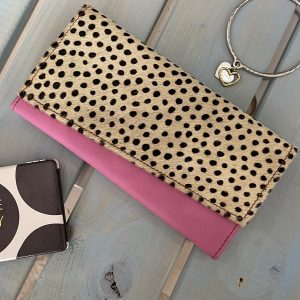 A recycled leather purse which has a bright pink leather main body and a black and white spotty print flap.