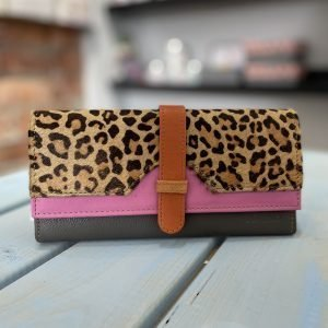 A recycled leather purse which has a bright pink and grey leather main body and a leopard print flap with a tan coloured strap fastening