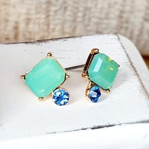 Vintage style stud earrings featuring a large baguette cut crystal in turquoise above a small sapphire crystal all set in antique gold