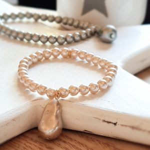 A single run of pink pearls with a pink droplet charm