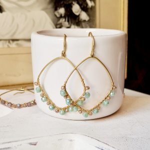 Gold hoop earrings on an ear hook. The hoops are threaded with jade and gold beads