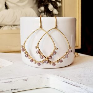 Gold hoop earrings on an ear hook. The hoops are threaded with lilac and gold beads