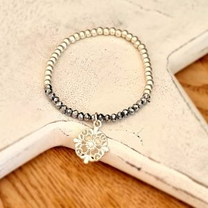 A bracelet with silver and grey crystal beads on an elasticated band with a silver circular floral charm