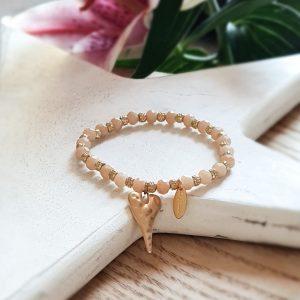 A matt gold heart charm on an elasticated bracelet of honey crystals and matt gold beads
