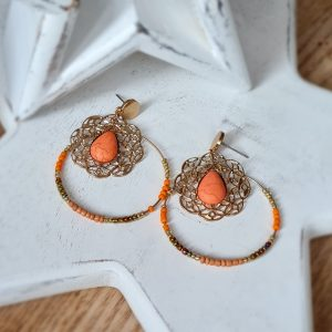 Bohemian Coral Earrings. A pair of gold hoop earrings with a coral stone