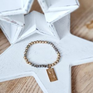 A bracelet of gold beads and coffee coloured facetted crystals on an elasticated band with a gold pin worked charm
