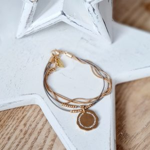 A Heavenly Circle Bracelet made of three gold snake chain strands and faux leather straps threaded with delicate gold beads and a beautiful gold and crystal disc