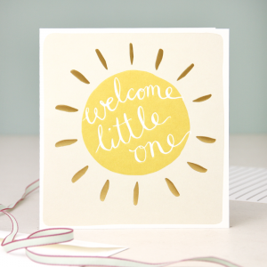 A neutral new baby card with a yellow and gold sun with welcome little one on the inside of the sun. blank inside