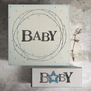A gorgeous solid wooden box which has been painted pale blue and has a lovely circular leaf design and the word Baby printed in the centre of it.