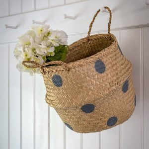 Natural seagrass hand woven belly basket with large grey polka dots and two carrying handles at the top