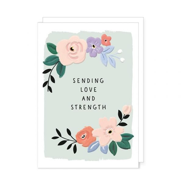 A card with sending love and strength on the front. Written on a pale blue background in black gloss with surrounding flowers in subdued colours with black gloss highlights. Blank inside