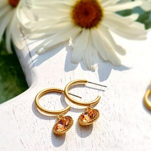 A demi hoop earring in old gold with a rose crytal drop