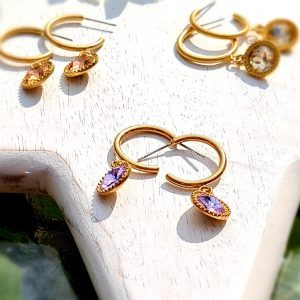 A demi hoop earring in old gold with a lilac crytal drop