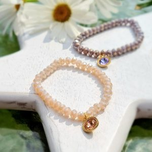 A crystal bracelet with nude crystals and a pink crystal charm