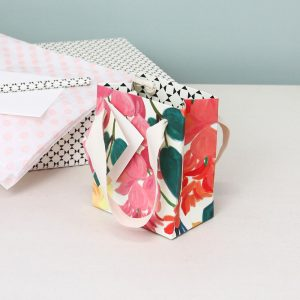 A floral small gift bag with red and pink flowers and green leaves and a black and white geometric inside.