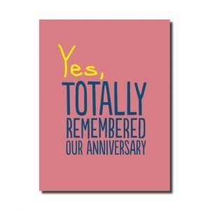 A pink card that says Yes, totally remembered our anniversary in yellow and black