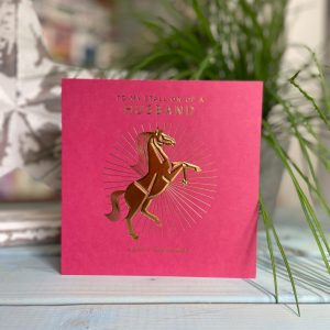 A red square card with a goild foil image of a horse on it and the words To My stallion of a husband printed on it.