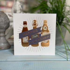A square card with an image of 3 bottles of beer with the words Brother Happy Birthday printed on it in a gold foil effect.