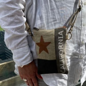 A canvas and leather cross body california patch bag. Made from canvas and recycled leather.