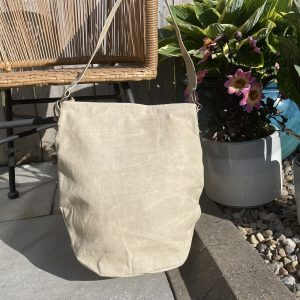 A beige coloured tote bag with adjustable strap. There are zipped pockets at the front of the bag and a printed stamp on it.