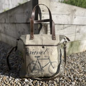 A medium size canvas and recycled leather handbag with leather handle straps and additional shoulder strap.