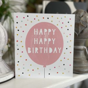 A colourful spotty card with a large pink balloon in the centre of it with the words Happy Happy Birthday printed on it.