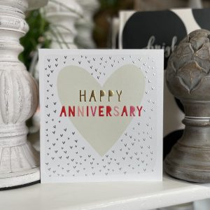 A white card with little silver hearts all over it and a large cream heart in the centre of it. The words Happy Anniversary are printed in multi coloured print in the centre of the heart.