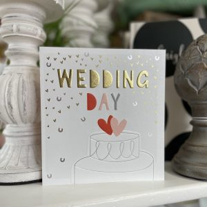 A lovely card covered with little gold hearts and silver horse shoes. there is an image of a wedding cake at the bottom of the card. The words wedding day are printed above the cake.