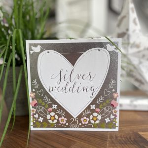 A lovely silver card with floral design and a large white heart with little white doves on it. The words SIlver Wedding are printed in the centre of the heart