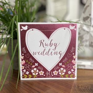 A lovely red card with floral design and a large white heart with little white doves on it. The words Ruby Wedding are printed in the centre of the heart