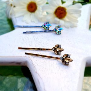 a pair of gold hair pins with a honey coloured crystal petal motif