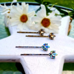 a pair of silver hair pins with a clear coloured crystal petal motif