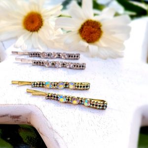 A pair of hair slides encrusted with iridescrent crystal stones