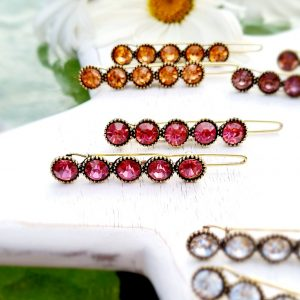 A pair of hair clips with a row of 5 crystals set in vintage gold. A choic of colours hony, rose, pink, clear or green