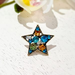 A star brooch pin with a twisted gold wire frame and colourful clear crystals in blues